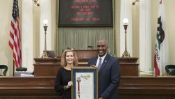 Assemblymember Cooper presenting Assembly Resolution to Debra Lynne on her retirement