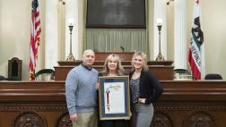 Jennifer Freeworth and her family with her retirement resolution on the Assembly Floor